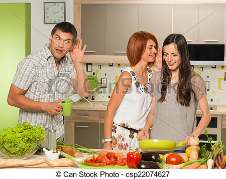 portrait of two beautiful caucasian women standing in kitchen cooking, laughing and whispering something, with one man behing them eavesdropping
